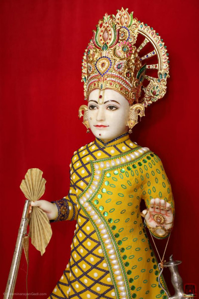 Divine darshan of Lord Shree Swaminarayan adorned in chandan vagha studded with pearls and bright green gemstones