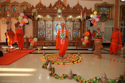 Divine darshan of His Holiness Acharya Shree Jitendriyapriyadasji Swamiji Maharaj at the centre of the magnificent patterns created with fresh coloured flowers arranged inside the mandir hall