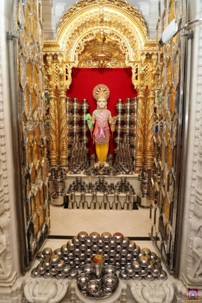 Divine darshan of Lord Shree Swaminarayan surrounded by beautifully arranged shinny steel utensils