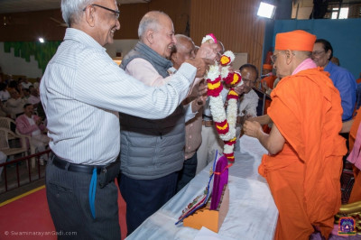 Professors, teachers, and former students of Shree Swaminarayan College put a garland on Acharya Swamishree Maharaj