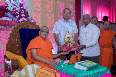 Acharya Swamishree Maharaj gives darshan to disciples who have offered a mugat for Lord Swaminarayan