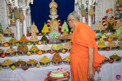 Acharya Swamishree Maharaj offers some prasad cake to Shree Harikrushna Maharaj