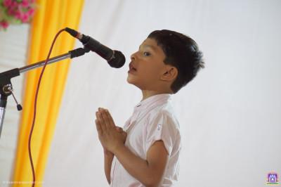 A young disciple says a prayer during his speech